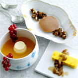 Three types of panna cotta with fresh berries, marinated raisins, sweet saffron soup and caramelised nuts